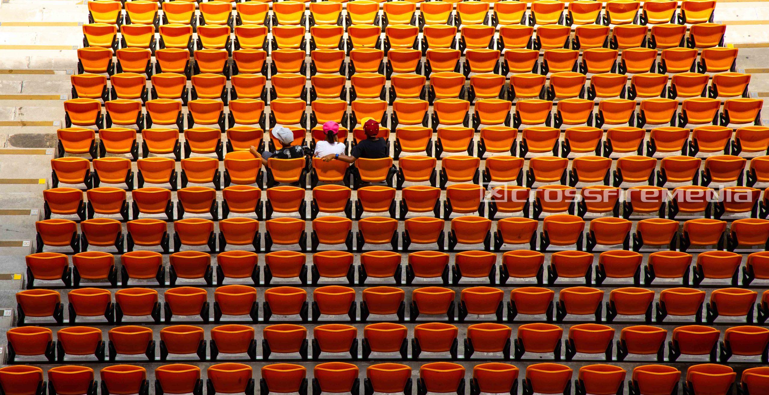spectators sit in stadium with orange seating