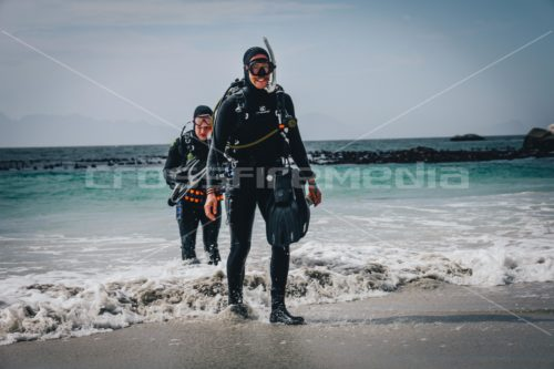 scubadiversin full scuba gear exit on a beach