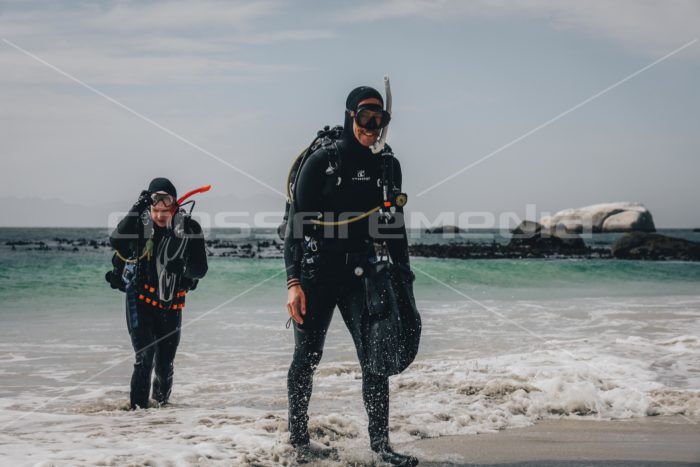 scuba divers walking out of the ocean on a beach