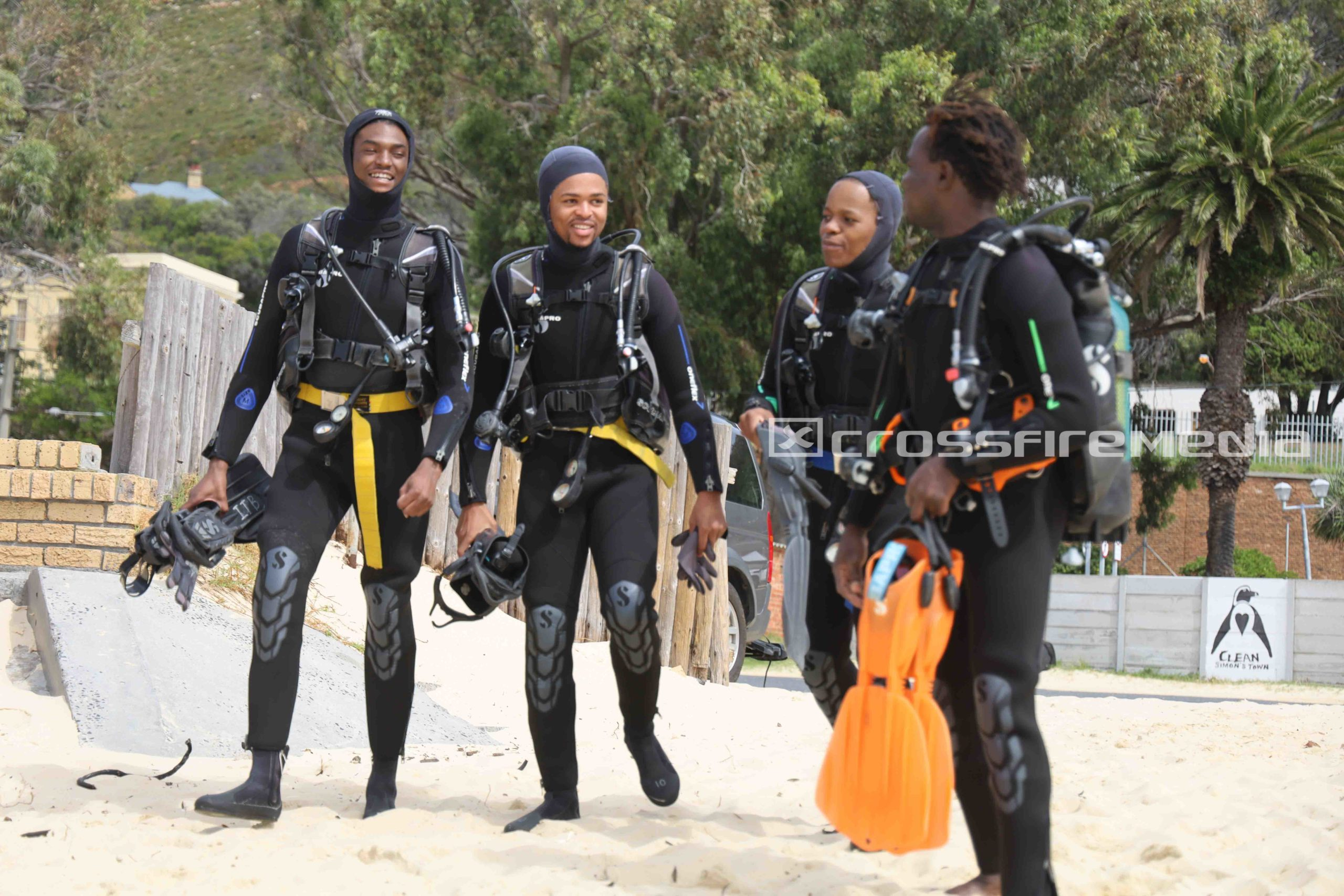 gallery image of divers in scuba gear on beach